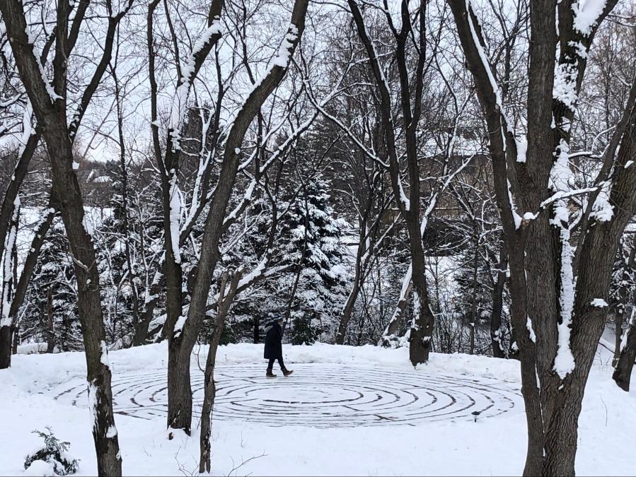 Woman walking on a snowy labyrinth.